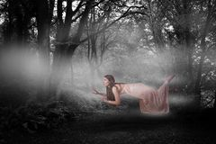Composite image of full length of woman levitating. Full length of woman levitating  against way between trees Royalty Free Stock Photo
