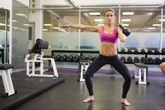 Full length of woman lifting kettle bell in gym. Full length of a serious young woman lifting kettle bell in the gym stock images