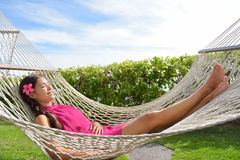 Full Length Of Woman Lying On Hammock In Park. Full length of happy relaxed young woman lying on hammock. Smiling mixed race Asian / Caucasian female is in dress Stock Photos