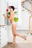 Full length of woman near the opened refrigerator Stockbild