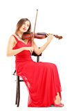 Full length of a woman in red dress playing the violin Royalty Free Stock Photos