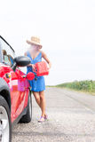 Full-length of woman refueling car on country road against clear sky Stock Image