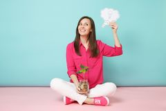 Full length of woman in rose shirt, white pants sitting on floor hold gold coins in glass jar isolated on bright pink royalty free stock photography