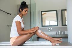 Full length of woman shaving leg in bathroom. Full length of young woman shaving leg by bathtub in bathroom stock image