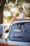 Full length of woman sitting on van Stock Photo