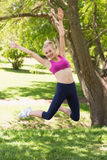 Full length of woman in sportswear jumping at park Royalty Free Stock Photo