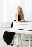 Full length of woman standing near the piano. Full-length portrait of woman in black dress standing near the piano with red rose on it. Concept of music and arts Stock Photos