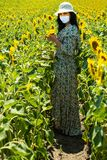 Full length of woman in sunflowers field during Covid19 Pandemic