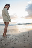 Full length of a woman in sweater standing on beach Royalty Free Stock Photo