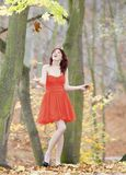 Full length woman in vibrant red dress playing with leaves in autumnal park Stock Photography