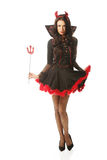 Full length woman wearing devil clothes, holding trident Stock Photo