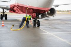 Worker Adjusting Chock By Airplane Wheels While Charging It. Full length of worker adjusting chock by airplane wheels while charging it on wet runway Stock Photo
