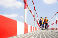Full-length of workers walking on footbridge against sky Stock Photography