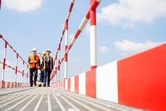 Full-length of workers walking on footbridge against sky royalty free stock photo