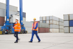 Full-length of workers walking in shipping yard Royalty Free Stock Photography