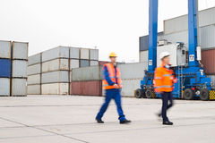 Full-length of workers walking in shipping yard Stock Images