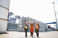 Full-length of workers walking in shipping yard Stock Image