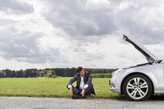 Full length of worried businessman sitting by broken down car at countryside Royalty Free Stock Photo