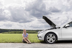 Full length of worried businesswoman sitting by broken down car at countryside Royalty Free Stock Photo