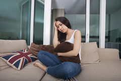 Full length of worried young woman sitting on sofa Royalty Free Stock Photo