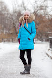 Full length young adorable blond woman wearing blue hooded coat strolling in snowy winter city park. Nature cold season freshness Royalty Free Stock Photos