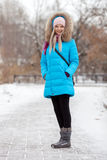 Full length young adorable blond woman wearing blue hooded coat strolling in snowy winter city park. Nature cold season freshness Royalty Free Stock Photo