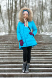 Full length young adorable blond woman wearing blue hooded coat strolling in snowy winter city park. Nature cold season freshness Royalty Free Stock Images