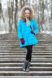 Full length young adorable blond woman wearing blue hooded coat strolling in snowy winter city park. Nature cold season freshness Royalty Free Stock Image