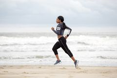 Full length young african american woman running on the beach by the water. Full length side portrait of young african american woman running on the beach by the royalty free stock image