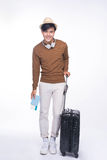 Full length of young asian man holding passport with suitcase ov Stock Photos