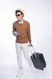 Full length of young asian man holding passport with suitcase ov Royalty Free Stock Photos