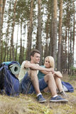 Full length of young backpacks relaxing in forest Royalty Free Stock Photo