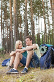 Full length of young backpacks relaxing in forest Royalty Free Stock Image