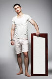 Full Length of Young Barefoot Man in White Shorts with Plackard. Handsome Male in White Shorts with Plackard posing Stock Photography