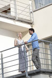Full length of young business couple conversing at hotel balcony Royalty Free Stock Image