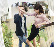 Full length of young business couple doing high-five on staircase Stock Photos
