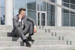 Full length of young businessman answering cell phone on steps outside office Royalty Free Stock Photo