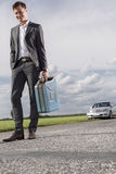 Full length of young businessman carrying gas can with broken down car in background at countryside Stock Images
