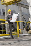 Full length of young businessman examining blueprint at construction site Stock Photography