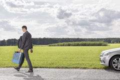 Full length of young businessman with gas can leaving broken down car at countryside Stock Photo