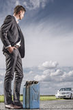Full length of young businessman with petrol can looking at broken car at countryside Royalty Free Stock Photography