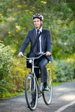Full length of young businessman riding a bicycle Stock Photo