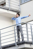 Full length of young businessman stretching at hotel balcony Stock Photos
