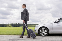 Full length of young businessman with suitcase walking by broken down car at countryside Royalty Free Stock Images
