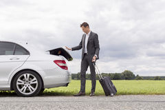Full length of young businessman unloading luggage from broken down car at countryside Royalty Free Stock Image