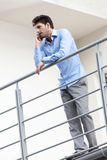 Full length of young businessman using cell phone at hotel balcony Royalty Free Stock Photography