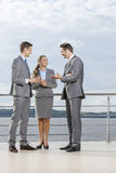 Full length of young businesspeople communicating on terrace against sky Stock Photo