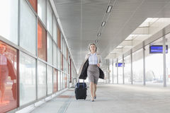Full length of young businesswoman with luggage rushing in railroad station Stock Photography