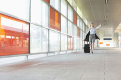 Full length of young businesswoman with luggage rushing in railroad station Royalty Free Stock Images