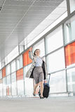 Full length of young businesswoman with luggage rushing in railroad station Stock Photos
